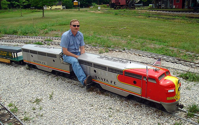 "Who's your ""chief"" ? This guy is. One of the Hesston Steam Museum volunteers operates a matched Santa Fe A-B pair of F7's on the museum's 1/8 scale railroad, hauling kids and kids-at-heart on a mile long loop of track."