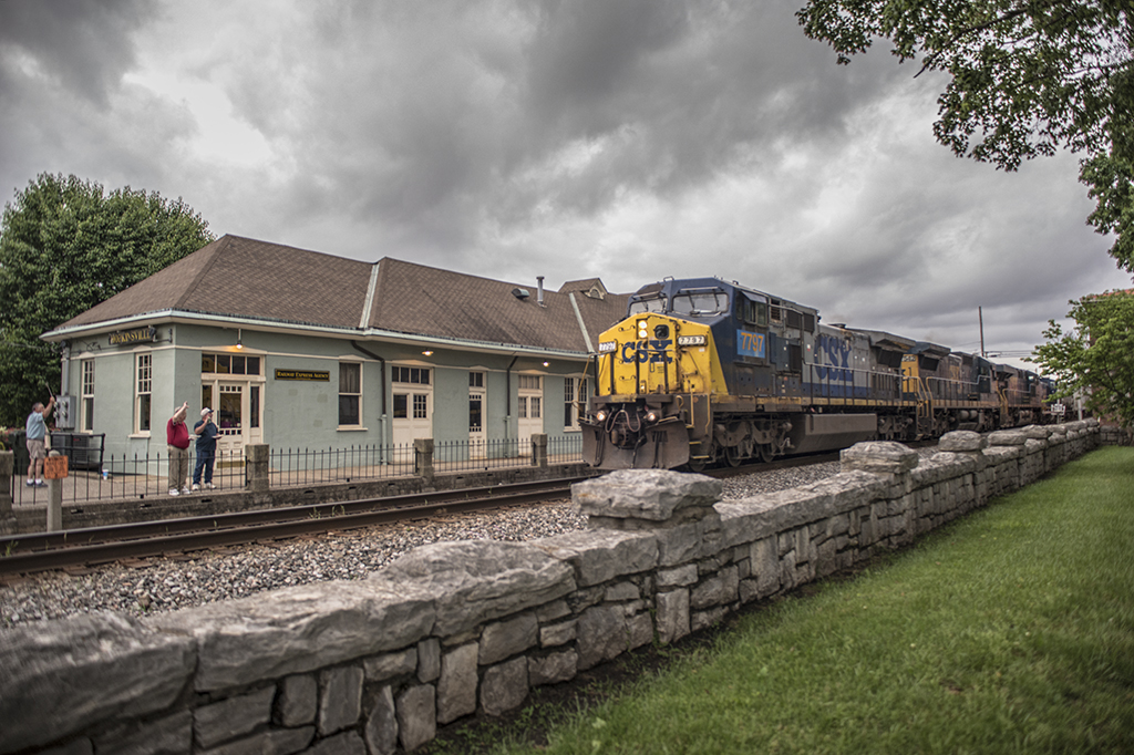 Some of the members of the West Kentucky Chapter of the National Railway Historical Society wave as a CSX southbound freight train passes the old L&N Depot as it heads south on the Henderson Subdivision at Hopkinsville, Ky. The chapter was having a cookout and meeting at the historic old depot - Jim Pearson