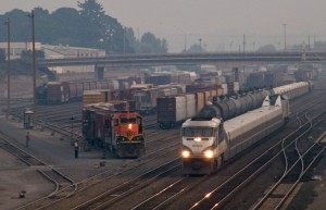 A Seattle bound Amtrak Cascades makes its way past BNSF's Vancouver yard as chopped nose SD9 #1550 works a cut of cars in the yard.