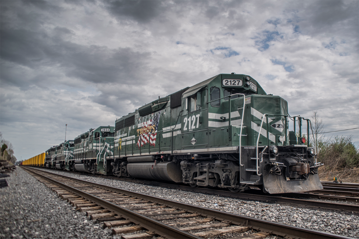 """March 30, 2016 - Paducah and Louisville Railway """"Salute to our Troops"""" engine 2127 heads up a ballast train sitting in the number 2 track at West Yard in Madisonville, Ky waiting for a crew to take it on south to pick up a load of rock. - Tech Info: 1/250 