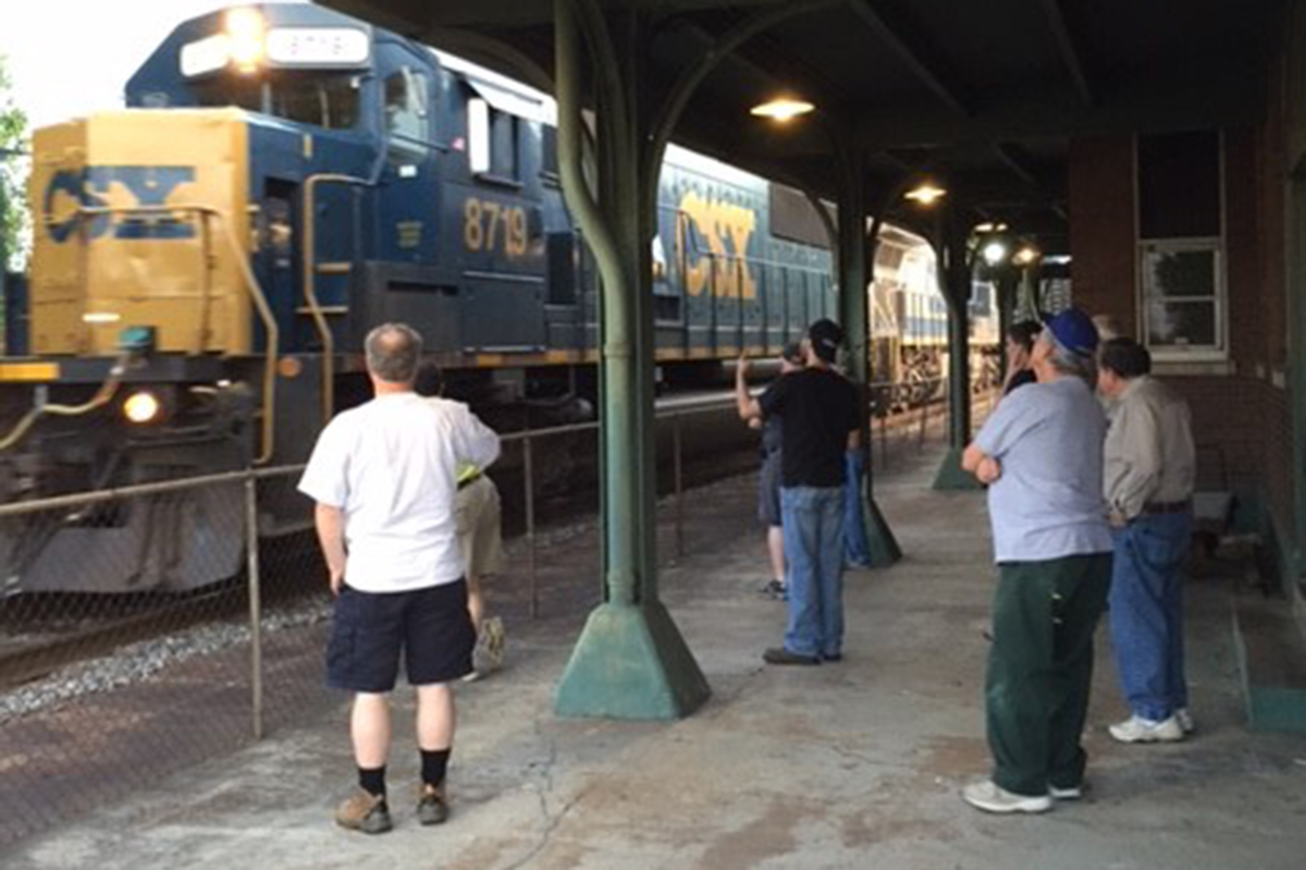 April 2016 meeting attendees take a break to watch a passing north-bound freight on CSX's Henderson Sub. - Photo by Ricky Bivins